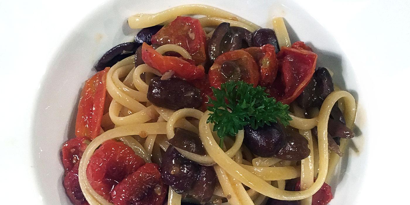 piatto di pasta con olive e pomodori