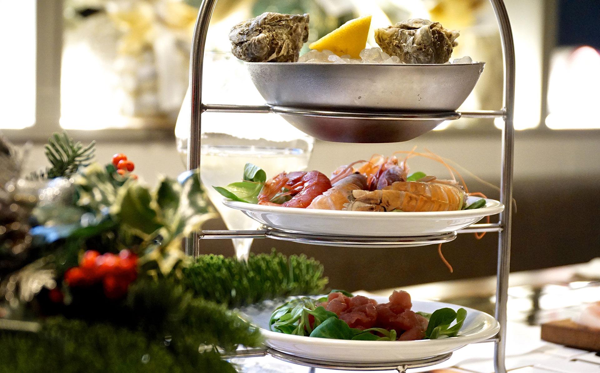 vassoi con ostriche e pesce crudo con decorazione natalizia