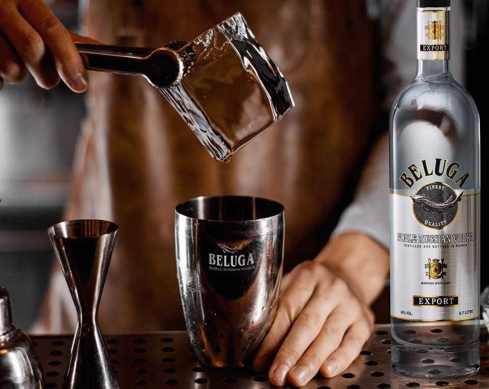 bartendere prepara un drink con vodka beluga e ghiaccio