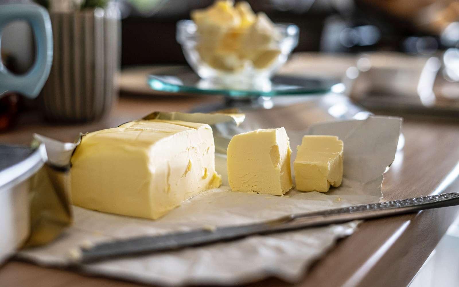 panetto di burro tagliato con coltello di acciaio